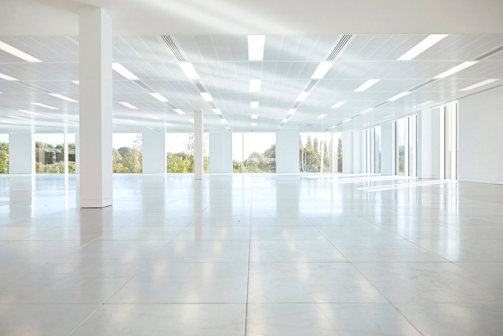 large space modern office interior with large windows by Airey Spaces