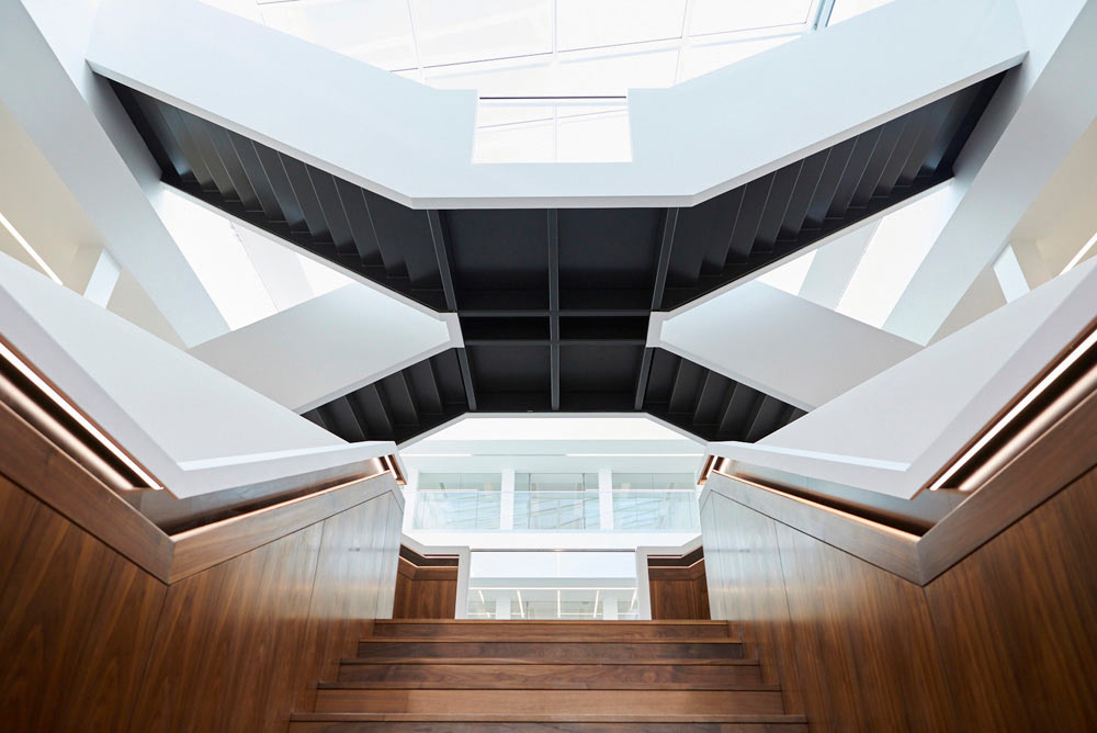 large modern staircase in atrium of new offices with wood and metal by Airey Spaces