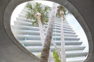 upward view of modern apartment building with palm trees in Miami by Airey Spaces