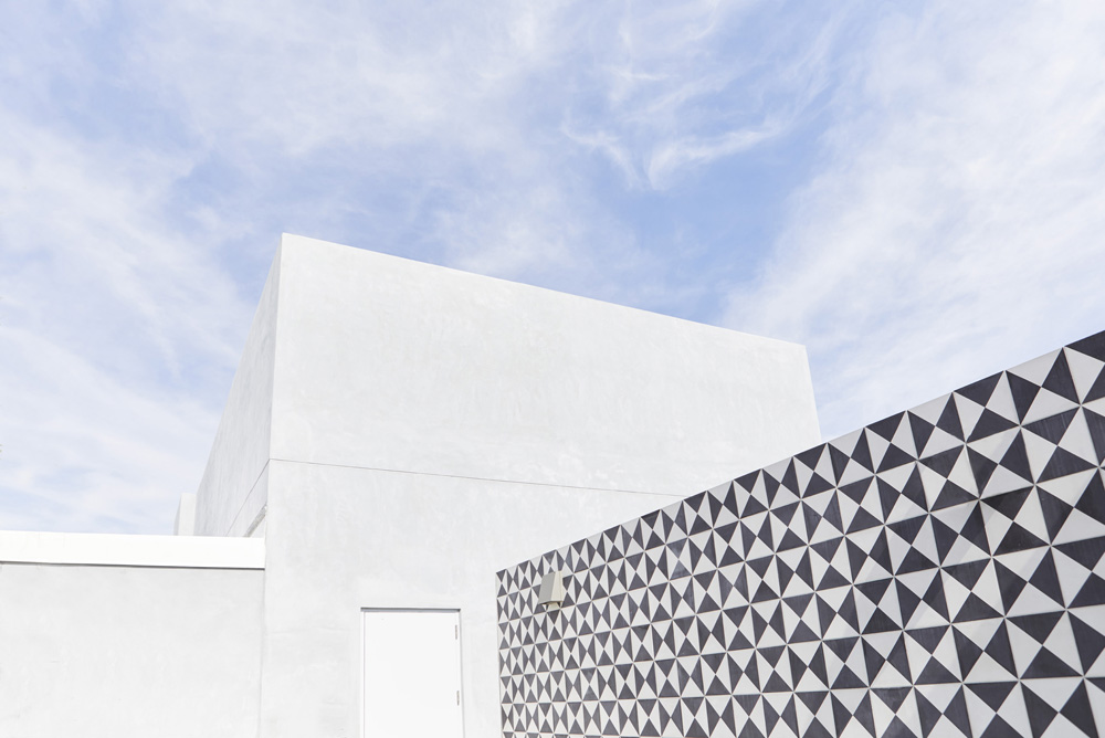 concrete and black and white tiling on rooftop of modern apartment building by Airey Spaces