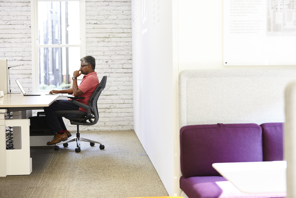 man in office chair at desk in modern office environment