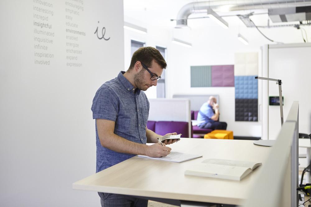 man stood at desk working in modern light office environment