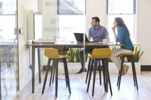 office meeting in modern glass environment with colourful furniture