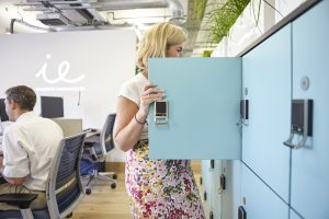 woman in modern light office with turquoise lockers