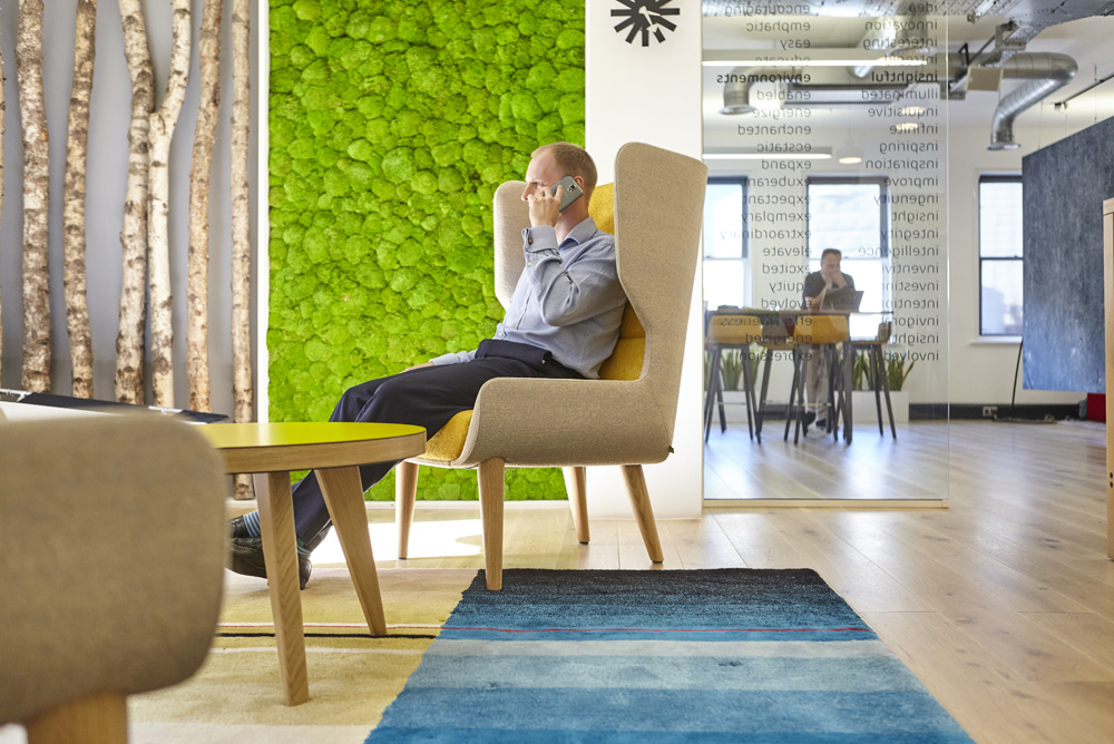 man on phone in modern chair in light colourful office with moss wall