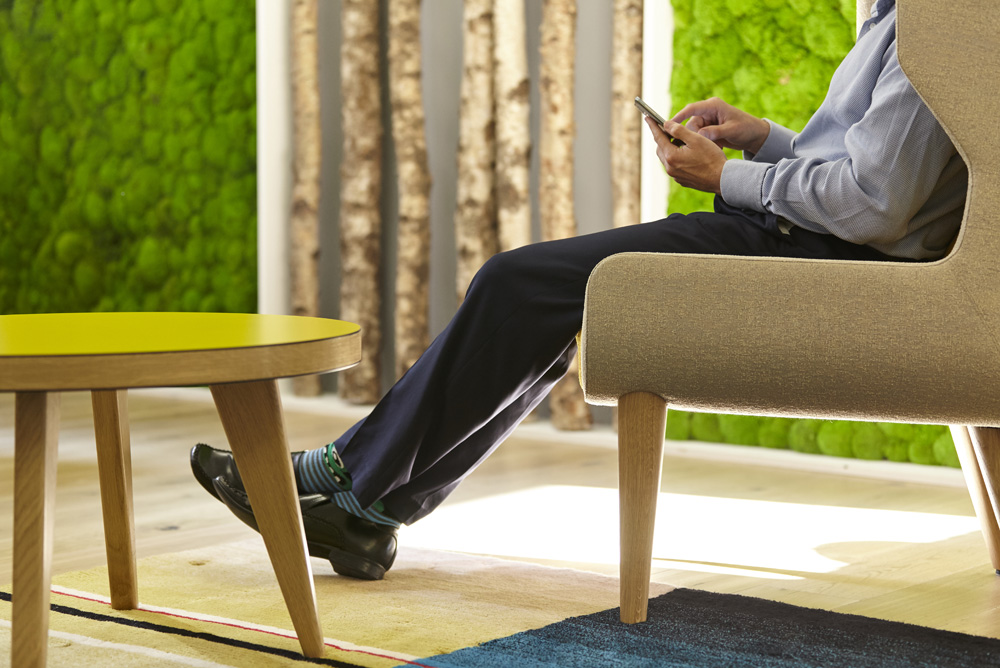 man on phone in modern office environment with moss wall