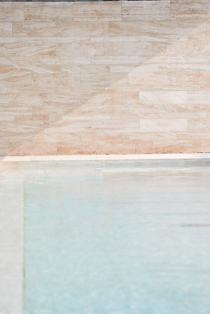 sunshine on swimming pool and marble wall at Muraba Residences by Airey Spaces