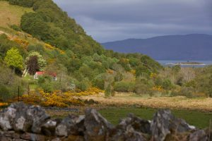 Scottish house with red tin roofs by Lake in Highlands by Airey Spaces