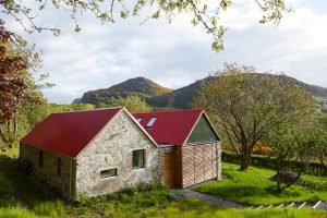 Scottish stone and timber clad house with red tin roof by Airey Spaces