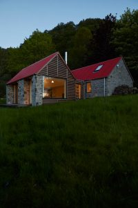 Scottish stone and timber clad house with red tin roof at dusk by Airey Spaces