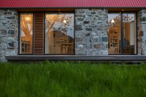 Scottish stone house with red tin roof by Airey Spaces