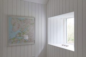 Scottish modern house interior with wood cladding and map by Airey Spaces