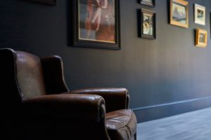 brown leather chair and dark blue wall with art by Velvet Orange Interiors