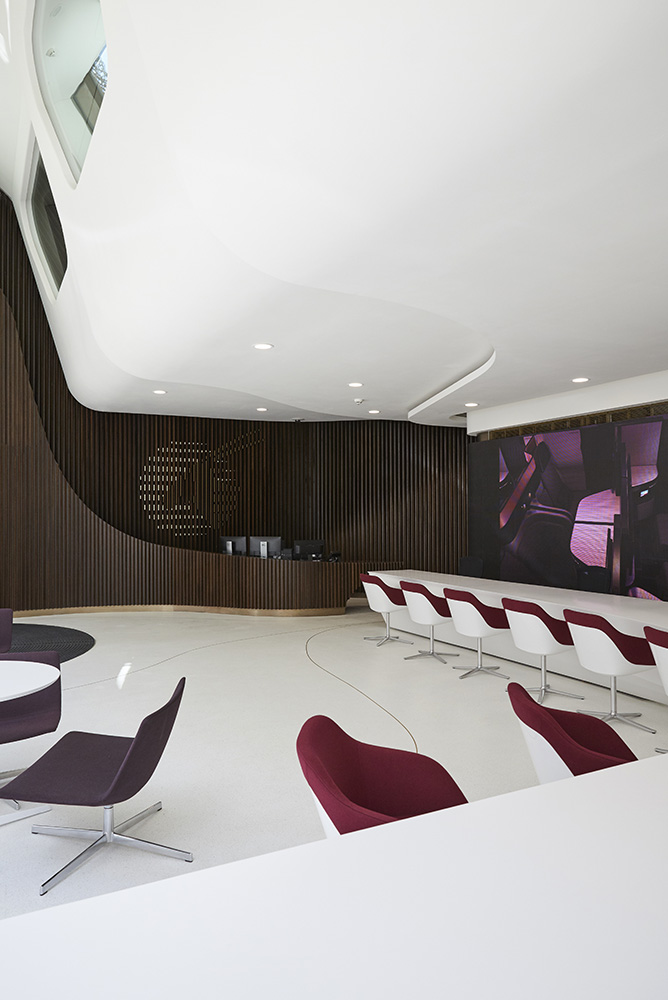 curvaceous modern reception interior with large white desk and wood cladding by Airey Spaces