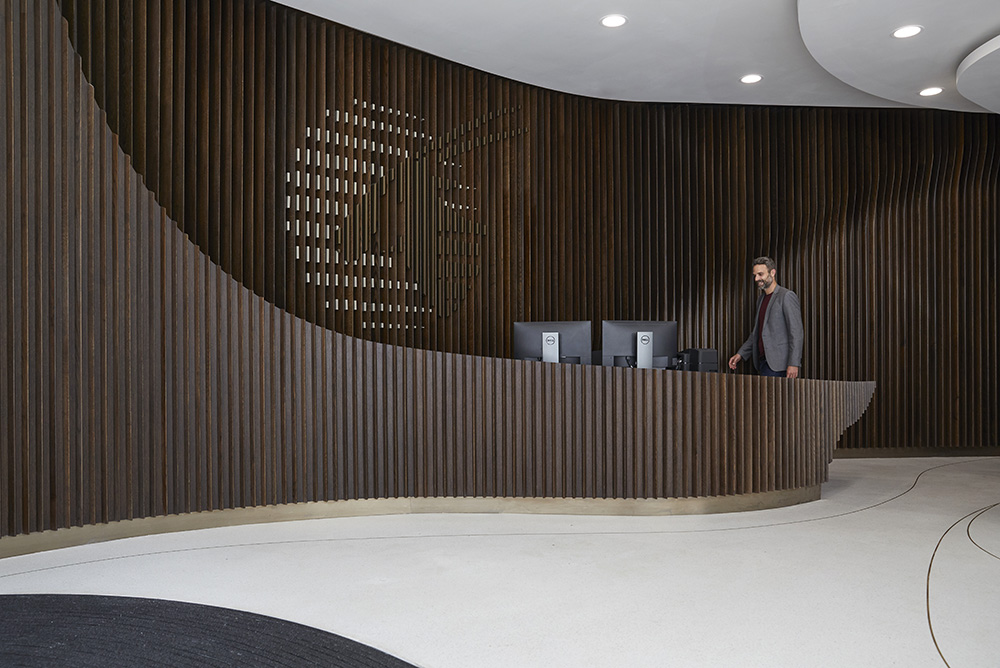 rich dark wood cladding in modern office large reception desk by Airey spaces