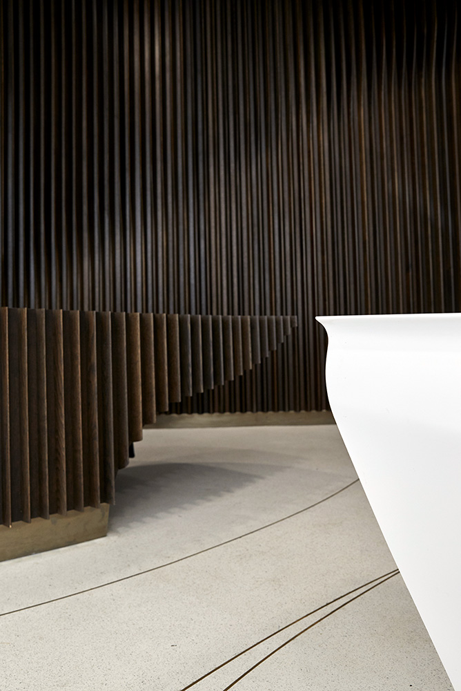 geometric symmetry in office reception contrast dark wood and white desk by Airey Spaces