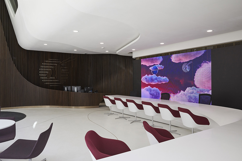 curved large modern reception interior rich dark wood cladding and white desk modern interior by Airey spaces